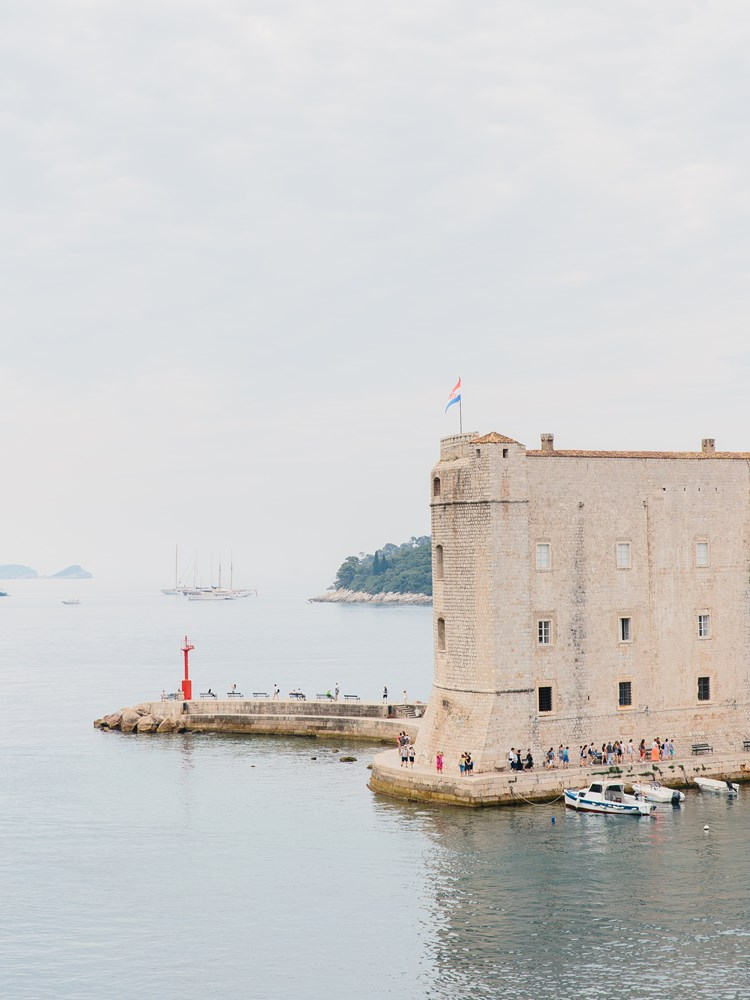 A picture of Dubrovnik harbour with a fortress building looking on to the sea
