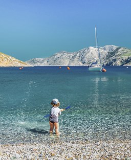 A child plays in the shallows of a cove with a pebbly beach and clear blue water.