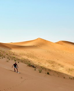 Picture of a desert with a snowboarder coming down the sand dunes