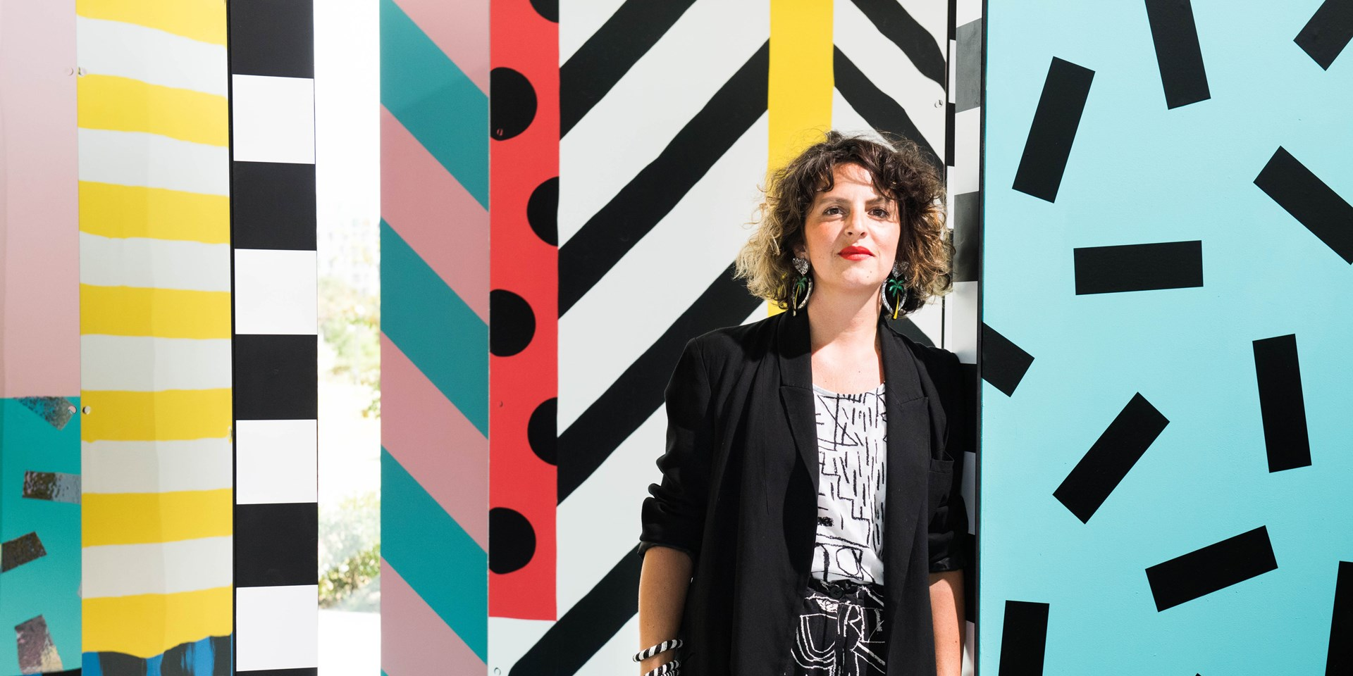 A portrait of Camille Walala against a colourful background that she designed