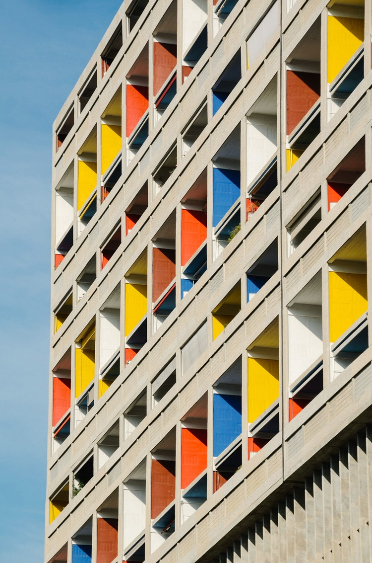 A close up of a modern building with colourful panels in the window designed by Le Corbusier