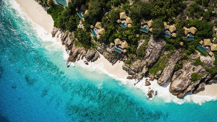 An image of a luxury resort from above with blue sea and a beach