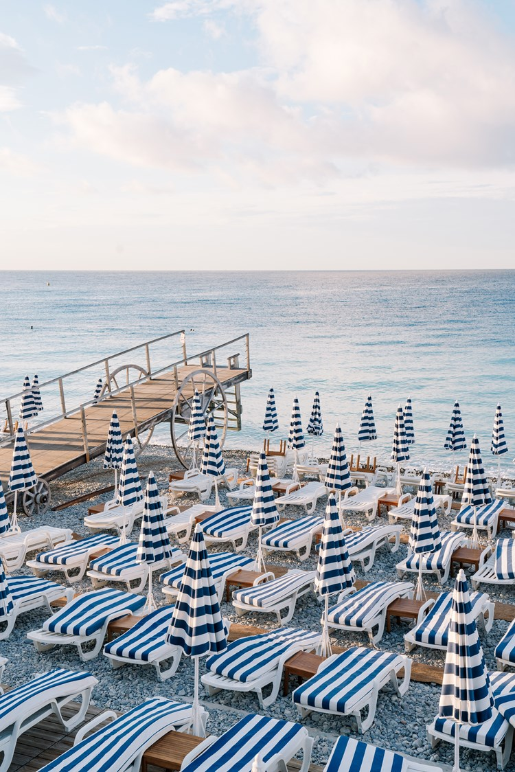 Blue and white folded parasols on a beach with small pier in Nice