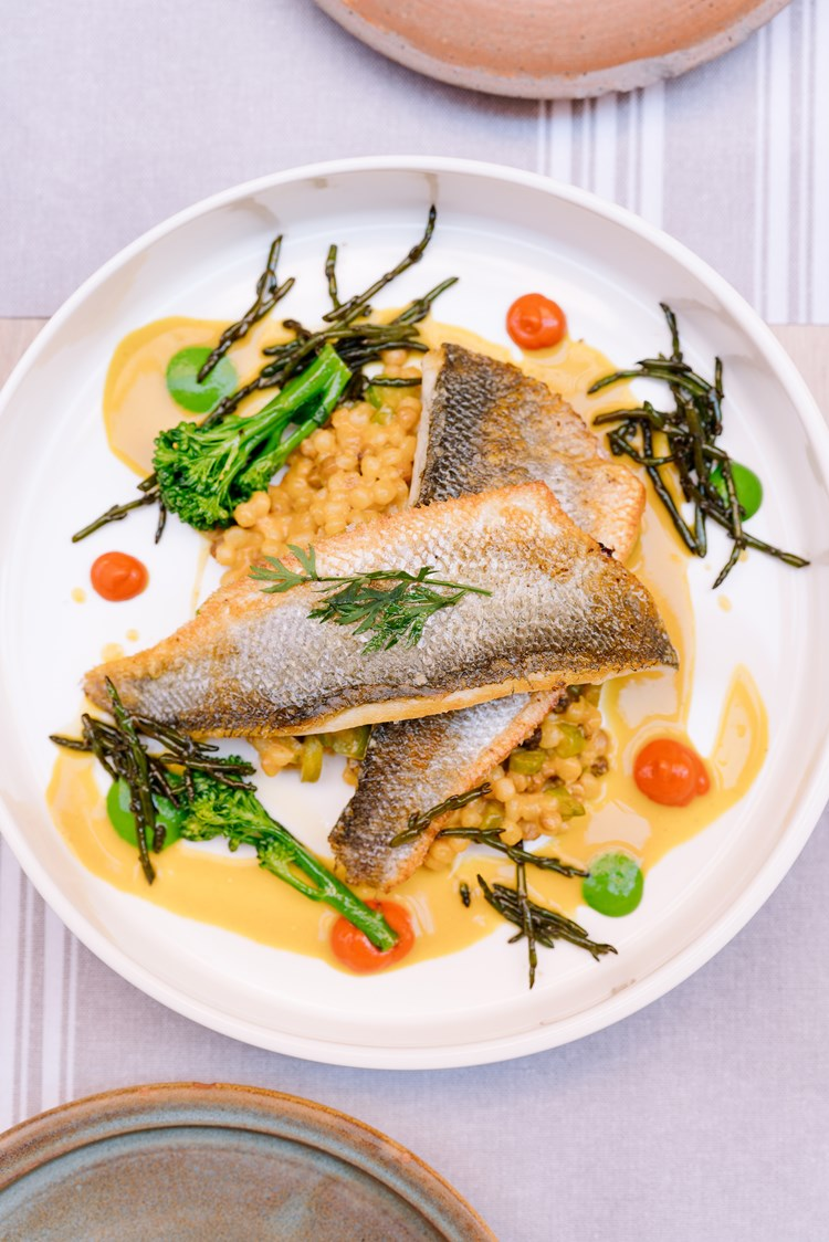 A plate of fish with crunchy green vegetables on a bed of fregola sarda at restaurant Le Panier