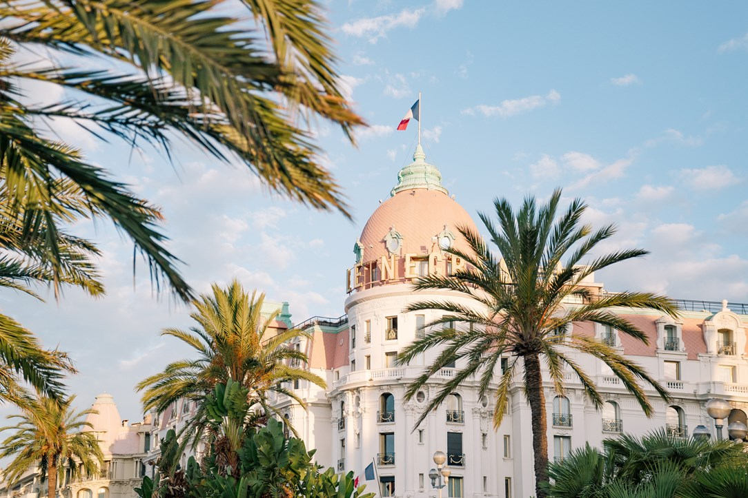 View of Le Negresco hotel from the ground. A small pink dome sits on top an imposing white building making up the hotel. Palm trees in the foreground