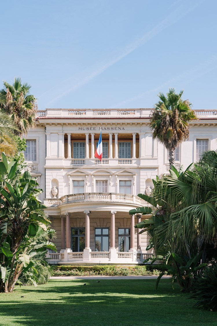 Shot of The Musée Masséna. A large white building with columns and tall windows. A flag waves in the centre and the grounds in front are visible with green grass and trees either side