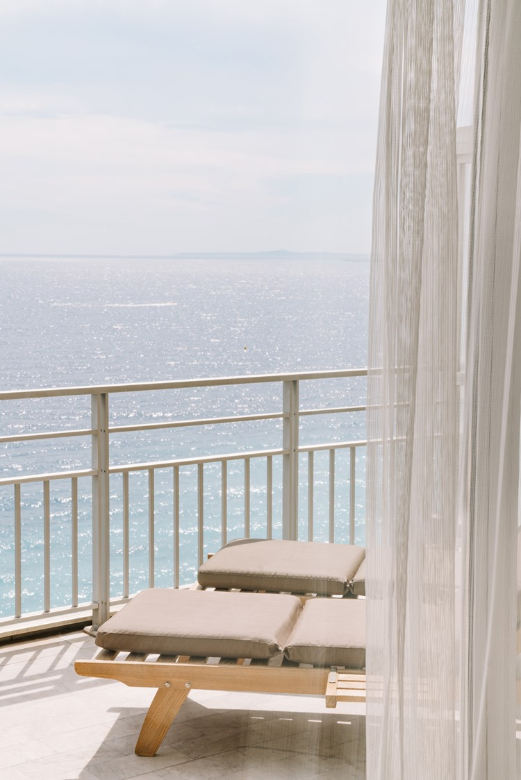 Sun loungers on the balcony of a hotel room with railings and the sea stretching to the horizon beyond them
