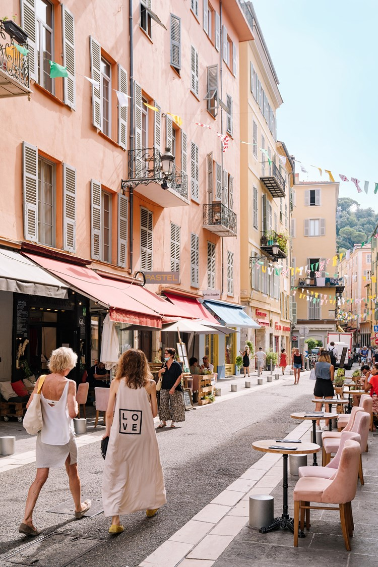 Two ladies walks down a small Nice street with where awnings reach out from shops and walls and chairs are various shades of pink and pastel