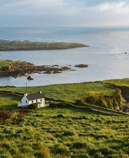 A remote white cottage with a slate roof sits on a rugged green outcrop by the sea