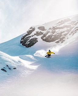 A figure in yellow ski gear slaloms between snow drifts on a rocky mountaintop