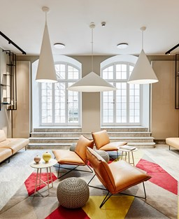 Hotel lounge area with tan leather soft seating, black bookshelves with ornaments, red and neutral marbled tile floor and steps up to French windows
