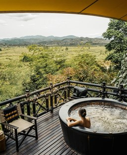 A woman sits in a wooden hot tub overlooking the jungle at The Four Seasons Tented Camp Golden Triangle, Thailand