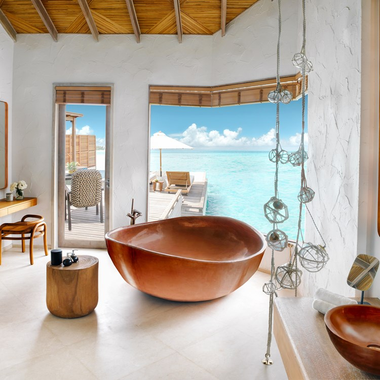 An oversized copper bath tub with infinity views of the open sea in the Maldives