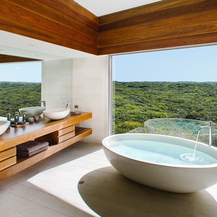 An oval hand-sculpted granite bath overlooking the coastal wilderness in Kangaroo Island, Australia