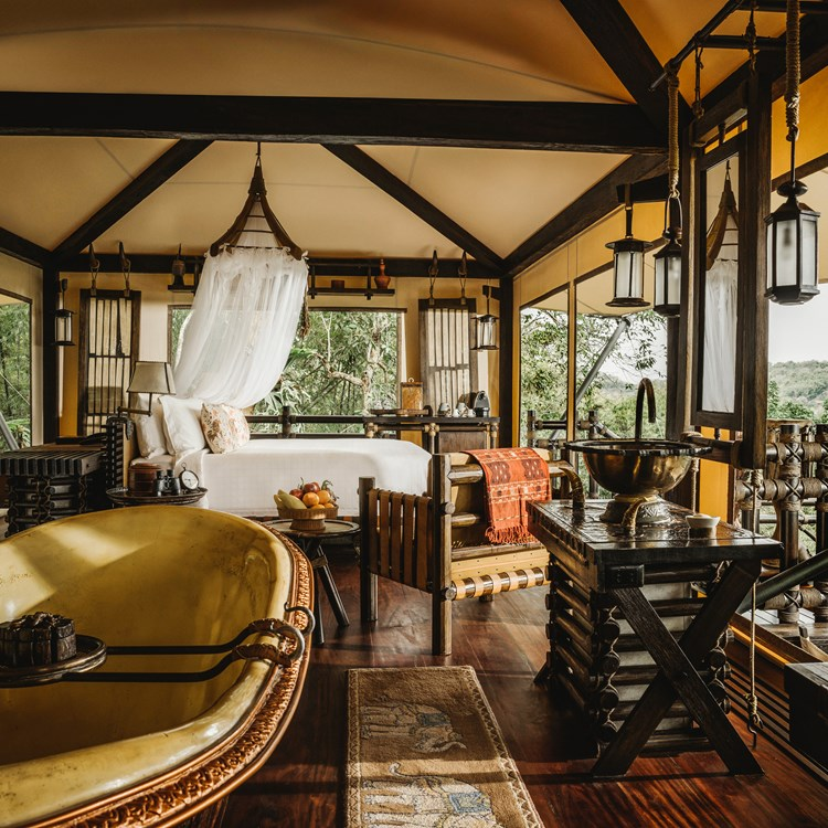 Interior shot of a luxury tent at the Four Seasons Tented Camp Golden Triangle, Thailand adorned with bespoke furnishings made from natural materials, and sumptuous king-size bed