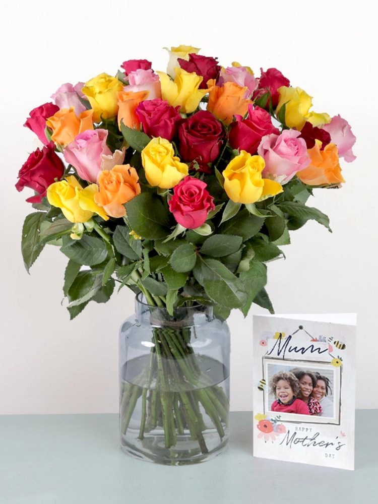 A bunch of red, pink, orange and yellow roses in a vase and a personalised Mother's Day card