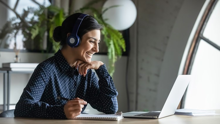 A woman wearing headphones and a navy polka-dot shirt smiles at something's she's reading on her laptop screen