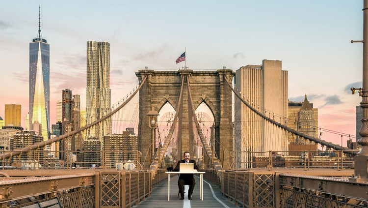 Author Ben Hammersley at his desk superimposed into the middle of a cityscape bridge
