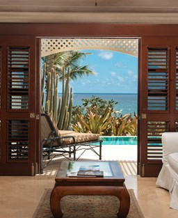 A living room in a hotel suite with a view of the Caribbean sea