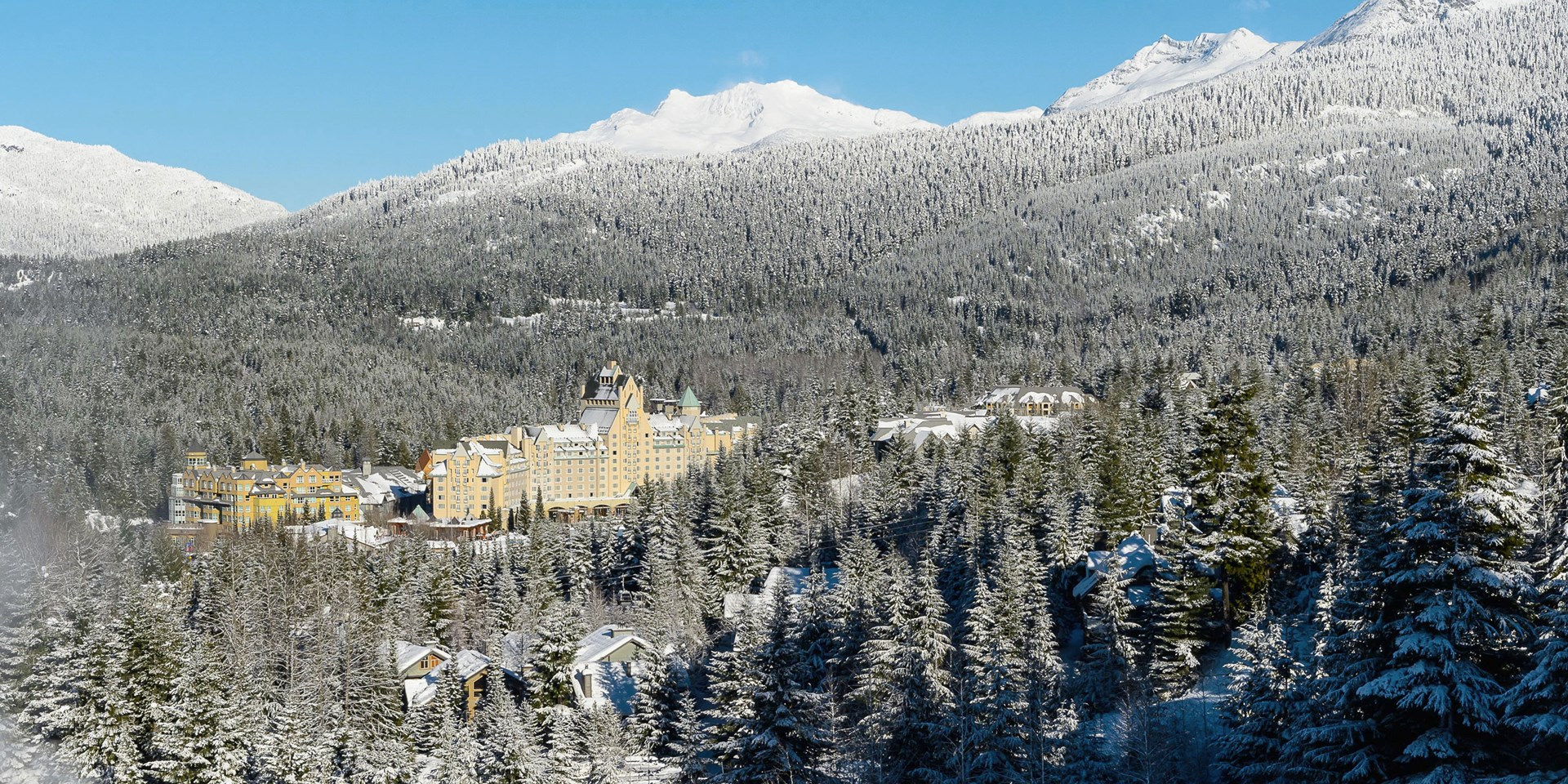 Mountains and forest covered in snow with a large hotel in the middle