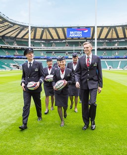 British Airways staff with rugby balls on a rugby pitch