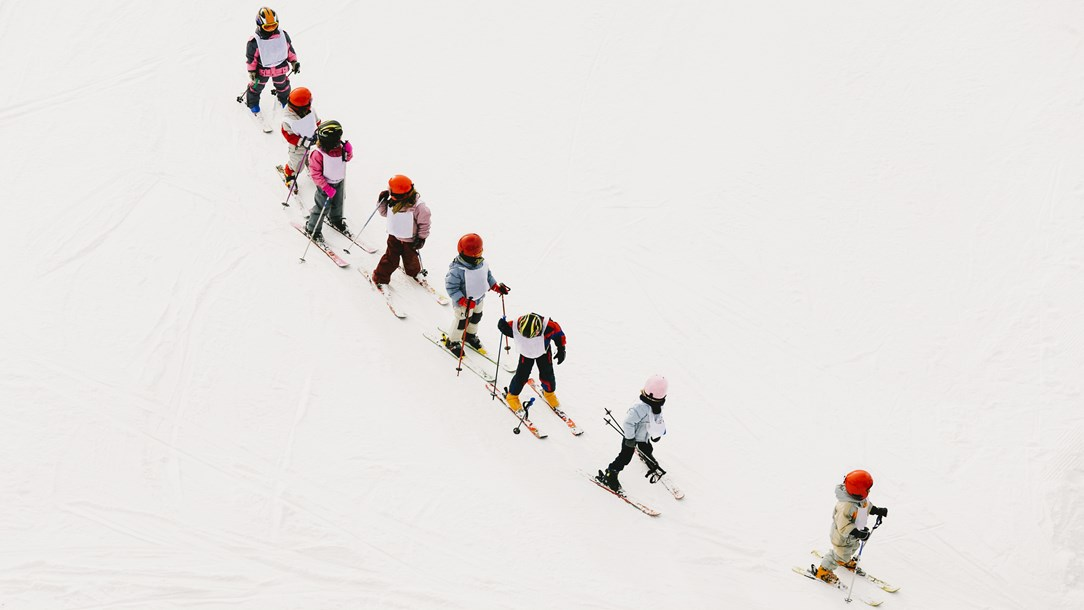 A group of children skiing in unison during a ski lesson