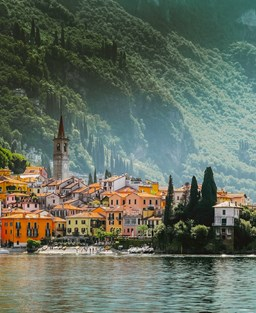 A picturesque, pastel-coloured town in Lake Como surrounded by water with a green, hilly backdrop