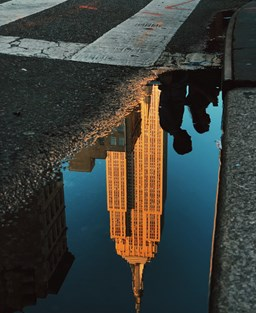 a reflection of a skyscraper in a puddle on a road