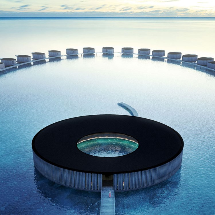 A modern circular building on the sea
