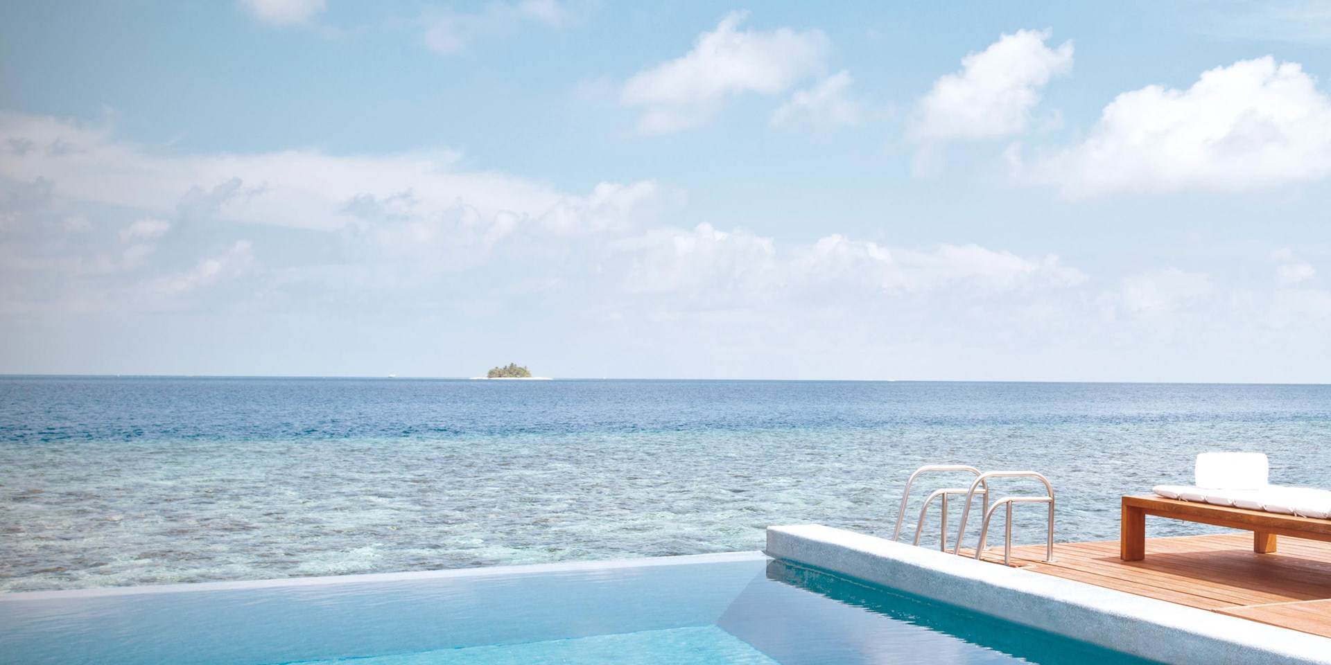 A swimming pool and sun loungers next to the sea in the W Maldives resort