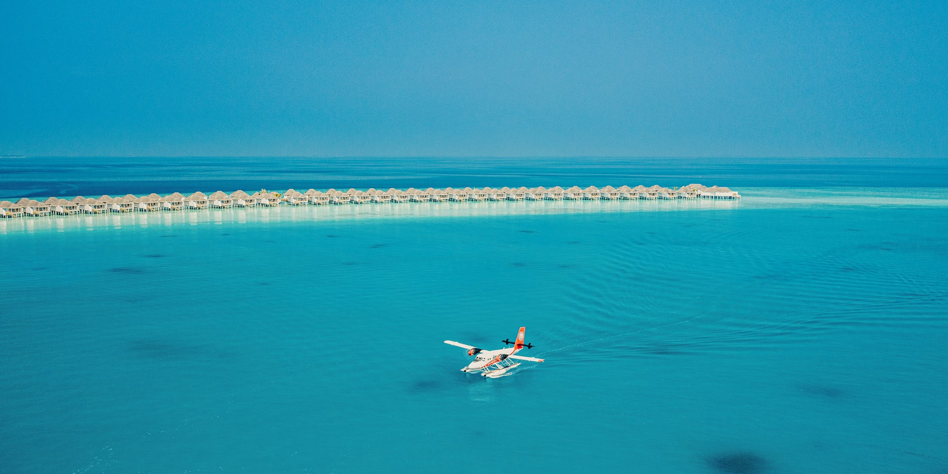 A seaplane coming to land on incredibly clear blue water