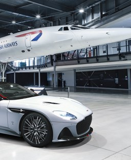 A stylish car in front of the Concorde plane in a hanger