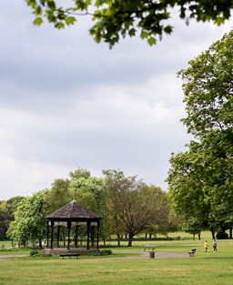 A lush green English part with a wooden bandstand