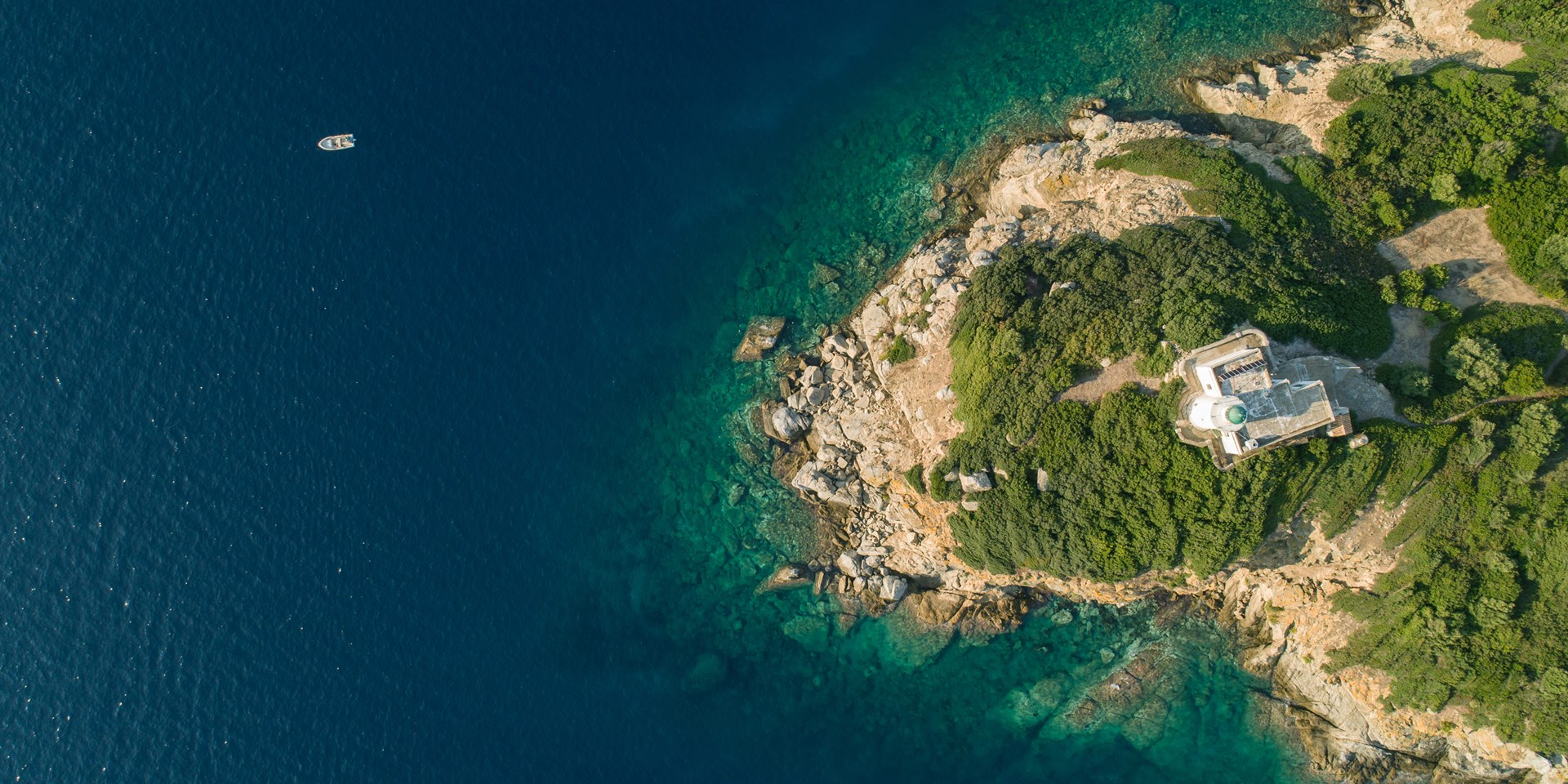 Aerial view of an island with a lighthouse on it
