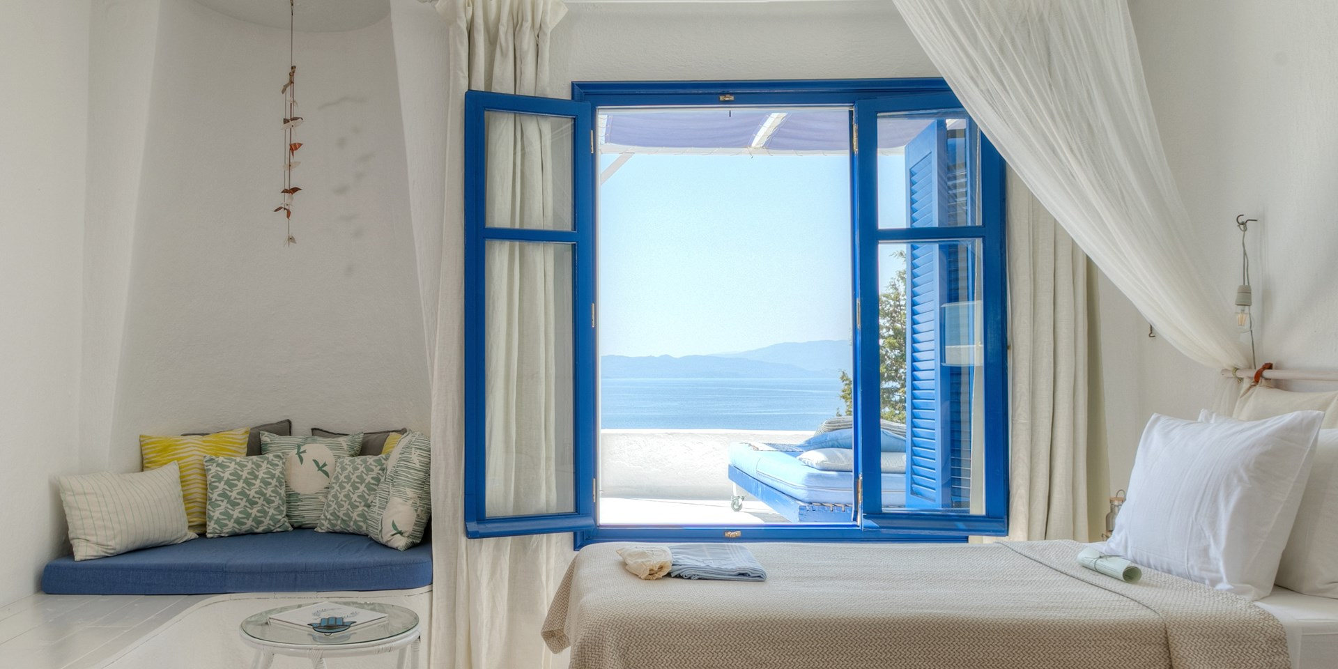 A room with a blue painted window and view of the sea
