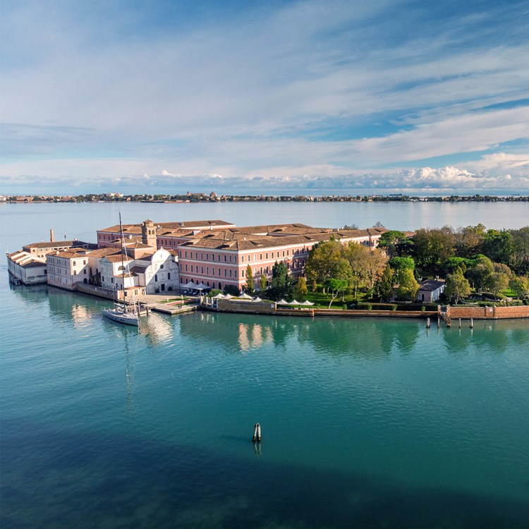 An island in a calm sea with a grand pink building and Italianate church