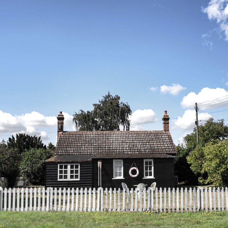 A traditional cottage with a picket fence and a lifebuoy handing outside