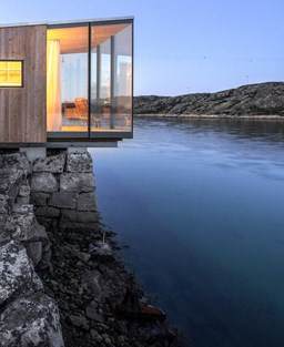 Modern scandi building perched on rocks next to water