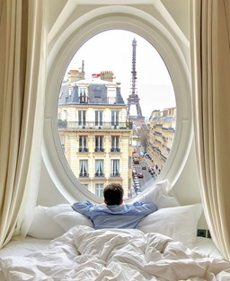 a man in bed looking out of a circular window at the Eiffel Tower